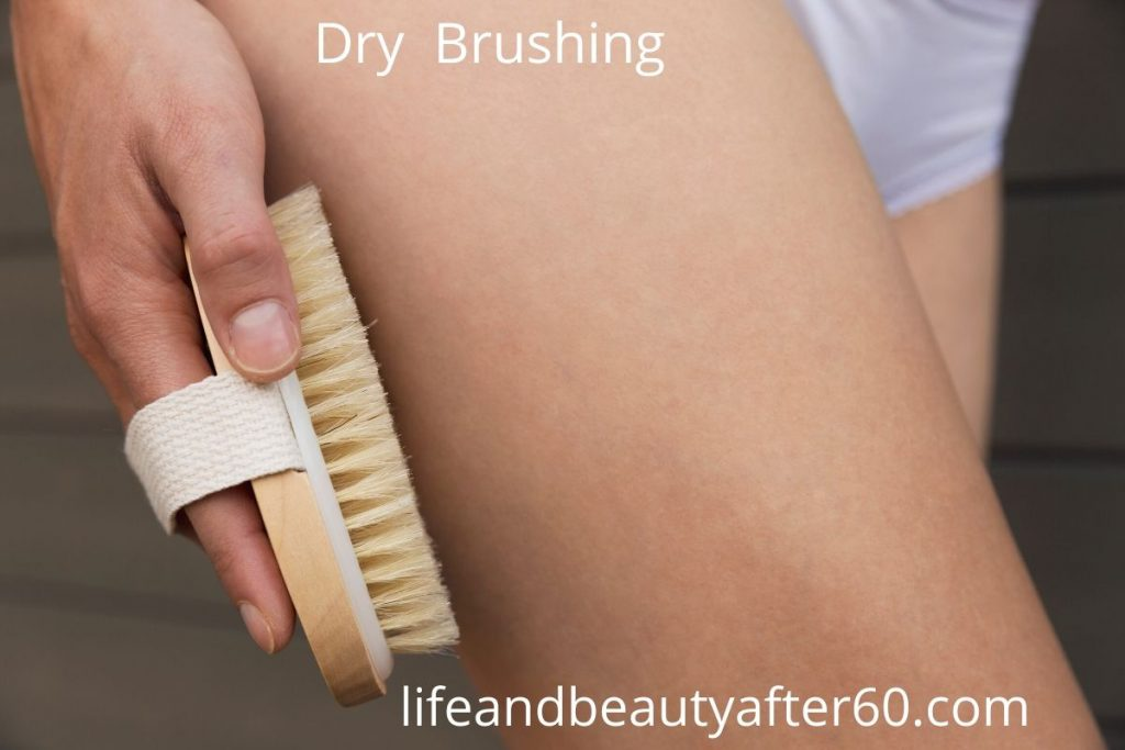 Lady with dry brush against leg skin