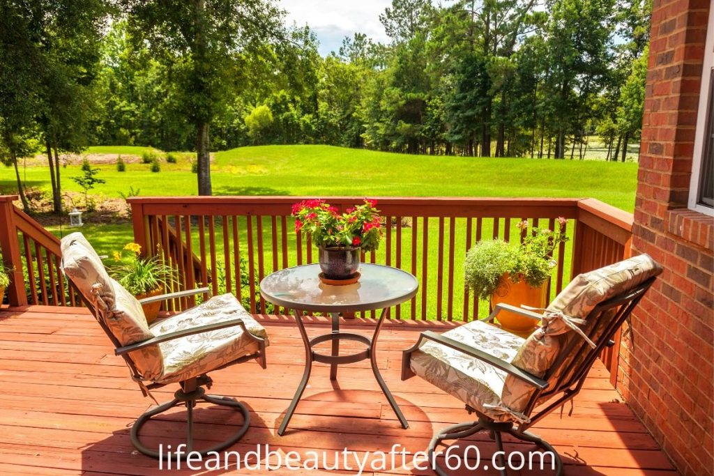 Outdoor seating on wooden deck overlooking lawn and trees.